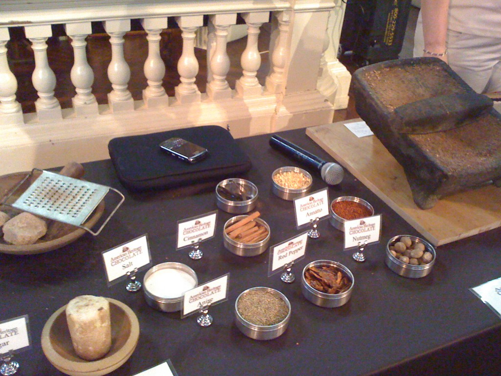 Ingredients used in colonial chocolate sticks on display, and the tool used for melting and grinding the nibs down on the right.